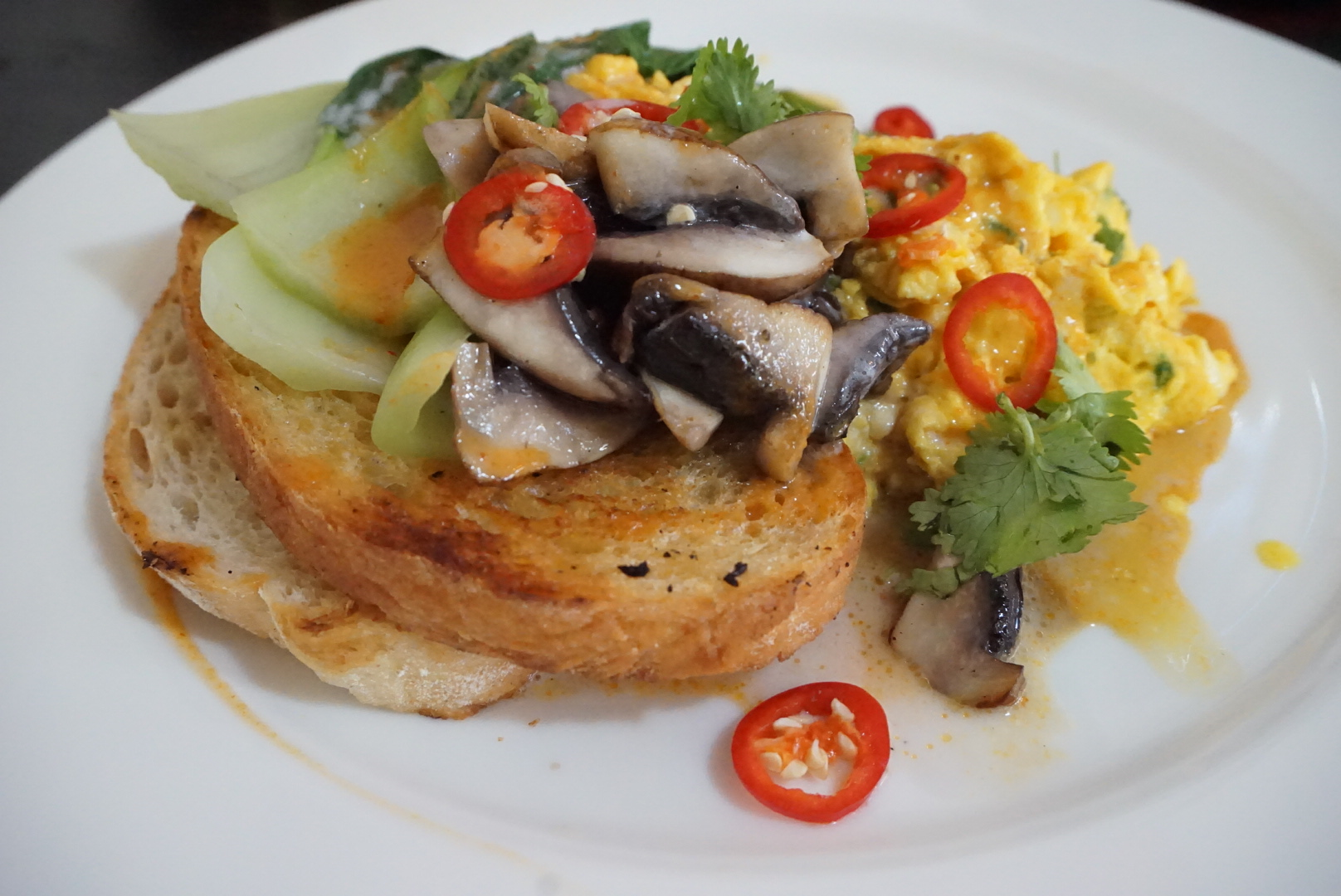 Scrambled eggs with cha-om, mushroom, bok choy, mild curry sauce on sour dough bread ($16)